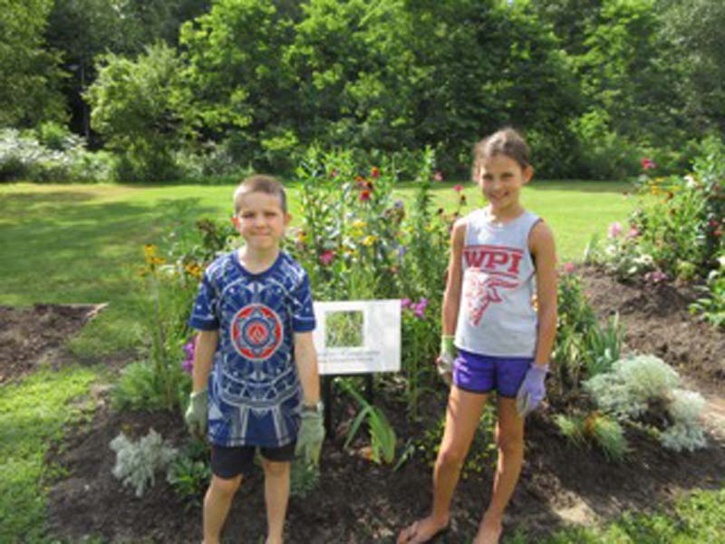 Two children standing in front of the raised bed, newly planted with perennials