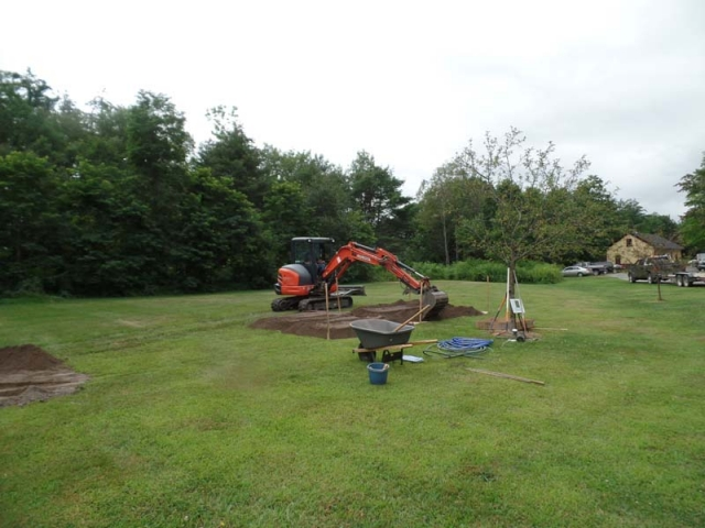 Mike begins spreading the compost/soil mixture into beds with the excavator