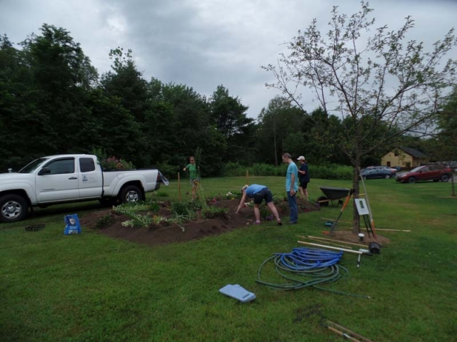 Four gardeners work on planting the beds under threatening skies!